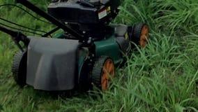 Hombres que siegan la hierba con un cortacésped metrajes