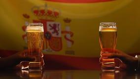 Hombres que sostienen los vidrios de cerveza, bandera española en el fondo, celebración del festival metrajes
