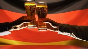 Hombres que tintinean los vidrios de cerveza, bandera alemana en el fondo, celebrando festival almacen de metraje de vídeo
