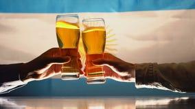 Hombres que tintinean los vidrios de cerveza, bandera argentina en el fondo, festividad nacional metrajes