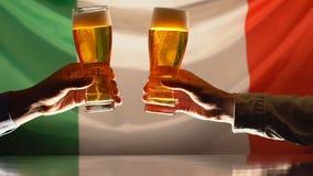 Hombres que tintinean los vidrios de cerveza, bandera italiana en el fondo, celebración del festival almacen de metraje de vídeo