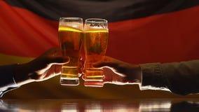 Hombres que tintinean los vidrios de cerveza contra bandera alemana en el fondo, celebración de victoria metrajes