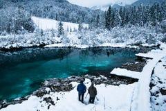 Hombres que toman las fotos en el zelenci hermoso en paisaje del invierno, Kranjska Gora, Eslovenia del lago del verde esmeralda Imágenes de archivo libres de regalías