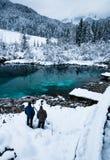 Hombres que toman las fotos en el zelenci hermoso en paisaje del invierno, Kranjska Gora, Eslovenia del lago del verde esmeralda Fotos de archivo libres de regalías