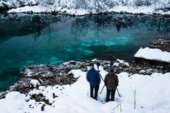 Hombres que toman las fotos en el zelenci hermoso en paisaje del invierno, Kranjska Gora, Eslovenia del lago del verde esmeralda Fotos de archivo