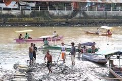 Hombres que trabajan en el fango de la orilla del río Fotos de archivo