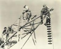 Hombres que trabajan en líneas eléctricas Imágenes de archivo libres de regalías