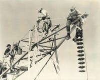 Hombres que trabajan en líneas eléctricas Fotografía de archivo libre de regalías