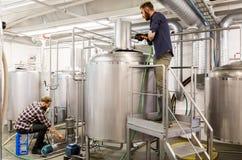 Hombres que trabajan en las calderas de la cervecería de la cerveza del arte fotografía de archivo libre de regalías