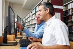 Hombres que trabajan en los ordenadores en biblioteca Imagenes de archivo