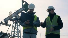 Hombres que trabajan junto cerca de las torres del aceite, cierre para arriba