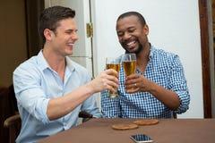 Hombres que tuestan los vidrios de cerveza en la tabla del restaurante Fotografía de archivo libre de regalías