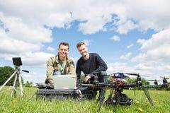 Hombres que usan el ordenador portátil al lado del UAV imagenes de archivo