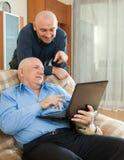 Hombres que usan el ordenador portátil en casa Fotografía de archivo libre de regalías