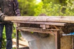 Hombres que usan la sierra de la circular para cortar la madera Imagenes de archivo