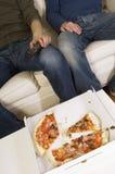 Hombres que ven la TV con la pizza comida mitad en la tabla Fotos de archivo libres de regalías
