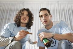 Hombres serios que ven la TV y que comen pizza con la cerveza Imagenes de archivo