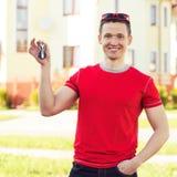 Hombres sonrientes con llaves de la nueva casa Imágenes de archivo libres de regalías