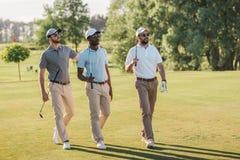 Hombres sonrientes en los casquillos y las gafas de sol que detienen a los clubs de golf y que caminan en césped Imagen de archivo