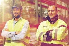 Hombres sonrientes en uniforme reflexivo en el almacén imágenes de archivo libres de regalías