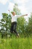Hombres sonrientes jovenes de salto contra prado del verano Foto de archivo