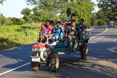 Hombres srilanqueses felices que montan un rototiller en un camino Foto de archivo