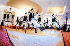 Hombres y bailarines de las mujeres que realizan danzas populares rumanas imagen de archivo