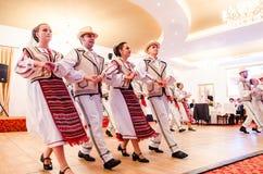Hombres y bailarines de las mujeres que realizan danzas populares rumanas imagenes de archivo