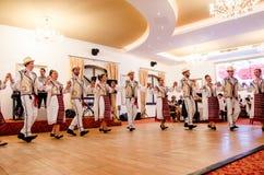 Hombres y bailarines de las mujeres que realizan danzas populares rumanas foto de archivo