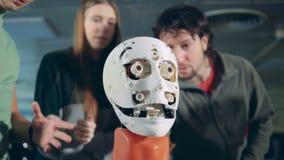 Hombres y charla de la mujer, controlando una cabeza robótica, cierre almacen de video