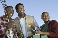 Hombres y muchacho que se preparan a la pesca con mosca imagen de archivo libre de regalías