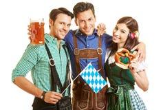 Hombres y mujer con la cerveza y el pretzel Foto de archivo libre de regalías