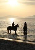Hombres y mujer en un caballo y una puesta del sol del oro Fotos de archivo