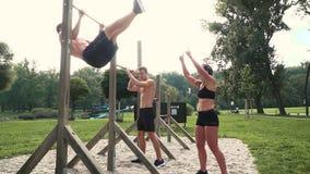Hombres y mujer que hacen diversos ejercicios del peso del cuerpo en la barra horizontal almacen de video