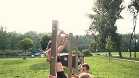 Hombres y mujer que hacen diversos ejercicios del peso del cuerpo en la barra horizontal metrajes