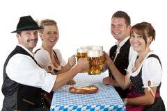 Hombres y mujeres bávaros con la cerveza de Oktoberfest Foto de archivo