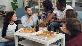 Hombres y mujeres de la gente joven que comen y que charlan durante partido interior en el apartamento almacen de metraje de vídeo