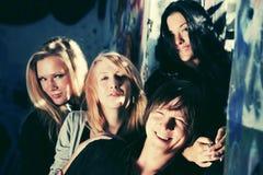 Hombres y mujeres de la moda de los jóvenes contra la pared de la pintada Fotografía de archivo