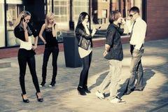 Hombres y mujeres de la moda de los jóvenes que invitan a los teléfonos móviles Fotos de archivo
