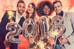 Hombres y mujeres que celebran el Año Nuevo 2018 Foto de archivo