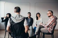 Hombres y mujeres que escuchan sobre los problemas de la ansiedad del adolescente durante terapia del grupo imagenes de archivo