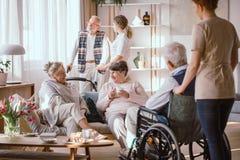 Hombres y mujeres que hablan en la sala común en clínica de reposo imagen de archivo