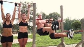 Hombres y mujeres que hacen diversos ejercicios del peso del cuerpo en la barra horizontal almacen de metraje de vídeo