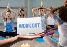 Hombres y mujeres que practican yoga en estudio de la aptitud con la mano que lleva a cabo el cartel en primero plano Imagen de archivo