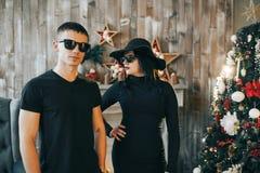 Hombres y una muchacha que se coloca delante de una chimenea cerca del árbol de navidad Fotos de archivo