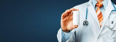 Hombro del doctor With A Stethoscope On que sostiene una botella de píldoras entre sus fingeres Concepto médico del hospital de l foto de archivo libre de regalías