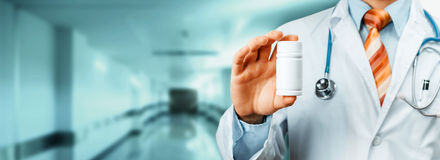 Hombro del doctor With Stethoscope On que sostiene una botella de píldoras entre sus fingeres Concepto médico del hospital de la  Fotografía de archivo