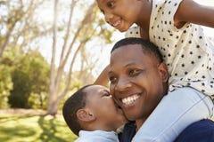 Hombros de Carrying Children On del padre como caminan en parque fotografía de archivo