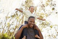 Hombros de Carrying Son On del padre como caminan en parque fotos de archivo