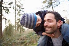 Hombros de Carrying Son On del padre durante paseo del campo fotografía de archivo libre de regalías